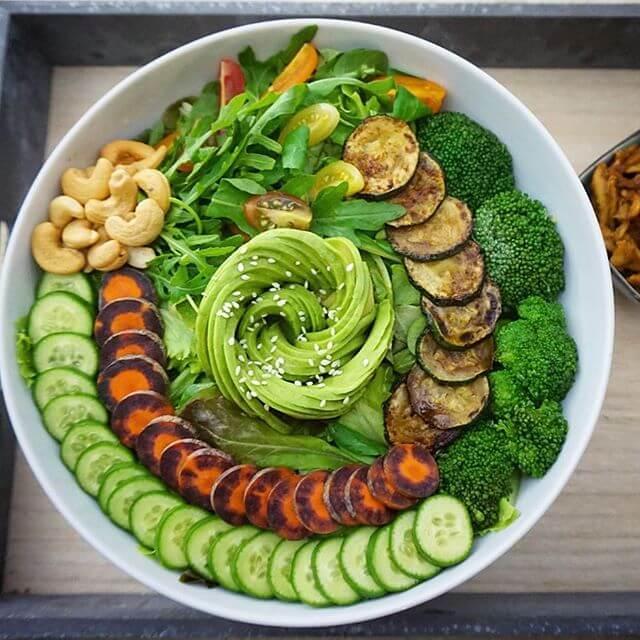 Dies ist eine Buddha Bowl mit Gemüse, Salat und Cashew Kernen.