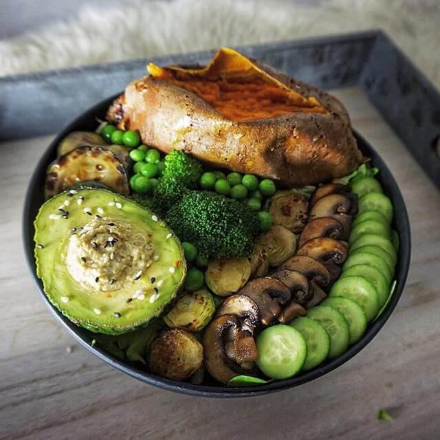 Dies ist eine Buddha Bowl mit Gemüse, Salat und einer gebackenen Süßkartoffel.